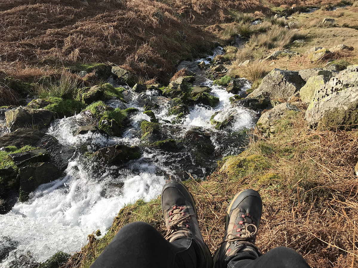 Sitting beside a waterfall in the Lake District, Cumbria